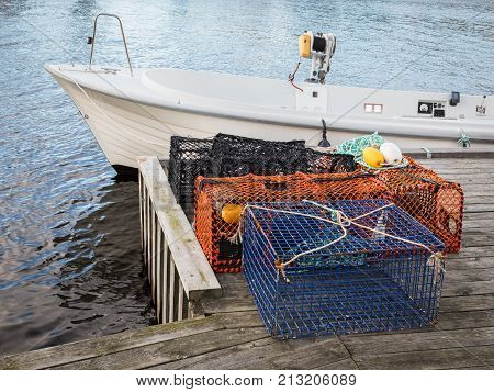 Traps for lobster and crabs standing on pier next to a white motor boat.