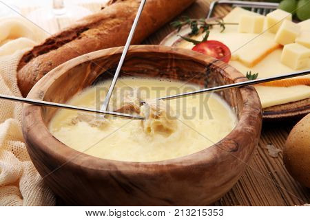 Gourmet Swiss fondue dinner on a winter evening with assorted cheeses on a board alongside a heated pot of cheese fondue with two forks dipping bread and white wine behind in a tavern