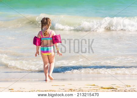 Little Girl On A Sandy Beach In Varadero, Matanzas, Cuba. Copy Space For Text. Back View..