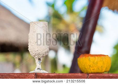 A Glass In The Sand On The Table, Varadero, Matanzas, Cuba. Close-up.