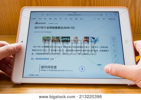 ZhongshanChina-November 122017:man reading mobile news saying the total online sales is 253.97-billion RMB on the Chinese online shopping day of November 11.