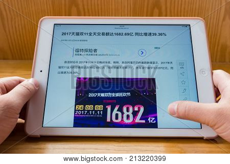 ZhongshanChina-November 122017:man reading mobile news saying Tmall sales 168.2-billion RMB on the Chinese online shopping day of November 11 39.36% more than 2016.