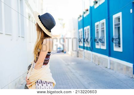 Unrecognisable young girl in hat,europe vacations,walking on a paved street