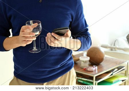 Torso of man holding glass of wine in one hand and using cell phone in the other