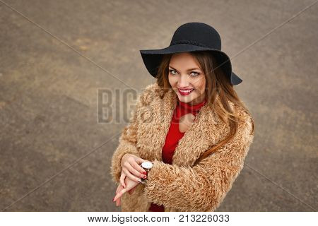 Young attractive girl outdoors in winter. She is wearing wide-brimmed hat and fur coat. The girl is standing next to fir-tree. She looks at clock how much time now