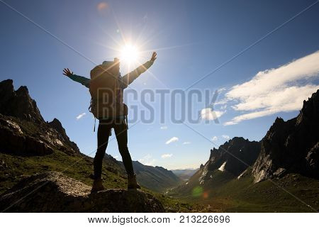 cheering woman with backpack hiking in mountains travel lifestyle success concep