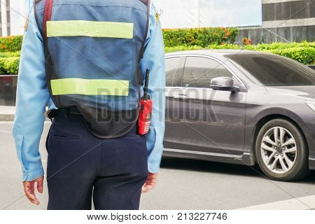 security guard walking by a patrol car on the street.