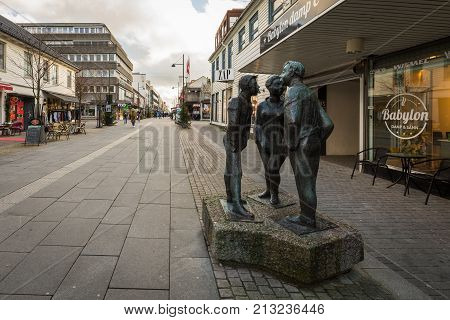 Kristiansand, Norway - November 8, 2017: The statue known as Paa Stripa in Markensgate, the pedestrian zone shopping street in Kristiansand. The statue is made by Arne Nikolai Vigeland, and shows three teenagers, one girl and two boys, talking.