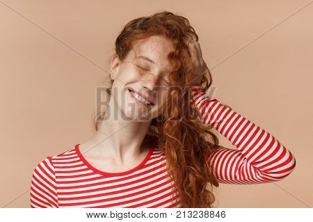 Horizontal Picture Of Young Attractive Redhead Lady Isolated On Peach Background Dressed In Striped