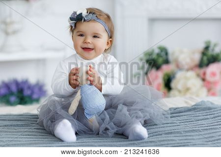 Little girl with brown eyes and red hair,but the head wearing a gray-blue wreath with white and gray flowers,dressed in a white t-shirt and transparent gray-blue skirt,spends time alone,playing on a large bed in the bedroom