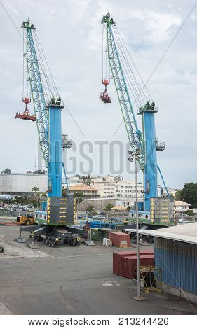 NOUMEA, NEW CALEDONIA, PACIFIC ISLANDS-NOVEMBER 25TH, 2016:  Two large cranes in commercial dock shipyard under an overcast sky in Noumea, New Caledonia