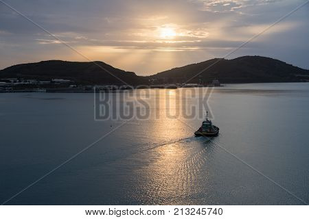 NOUMEA, NEW CALEDONIA, PACIFIC ISLANDS-NOVEMBER 25TH, 2016: Pilot boat at sunset on the Pacific Ocean waters with the island landscape in Noumea, New Caledonia.