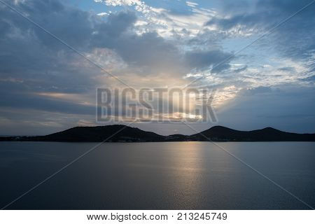 Sunset sky over remote Noumea, New Caledonia with island landscape silhouette and Pacific Ocean waters.