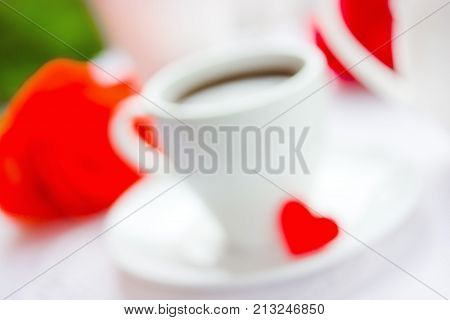 Festive blurred background on Valentine's Day. White cup of coffee rose and red heart. Breakfast for beloved. Love concept