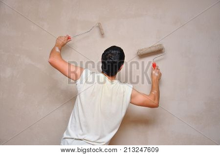 Man painting wall at home with painting roller. Repair home concept. Worker with paint on him after all day painting walls