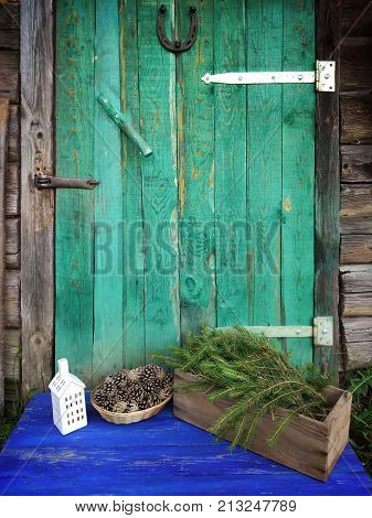 Decor of dry pine cones house lantern and fir tree branches in a wooden box on aged weathered wooden door background with horseshoe.