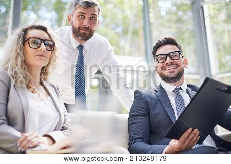 Talented group of managers in formalwear looking away with interest while having productive working meeting at modern boardroom, panoramic windows on background