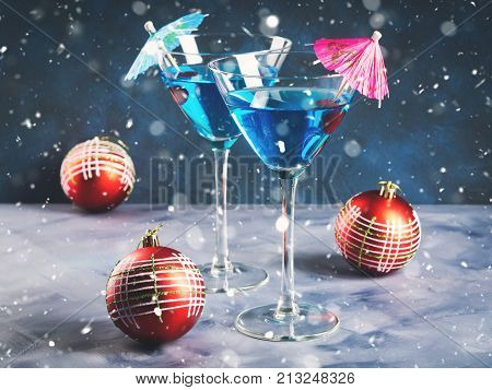 Blue cocktail in martini glass with umbrella and cherry. Festive drink for Christmas holiday party. Snow fall effect