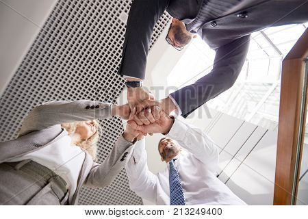 Low angle view of confident white collar workers joining hands together while standing at office lobby and supporting each other before important negotiations with business partners.