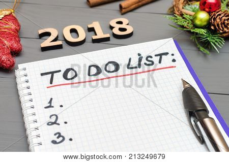 2018 to do list paper page with pan and New Year ornaments on the wooden desk table surface with copy space. To do list 2018