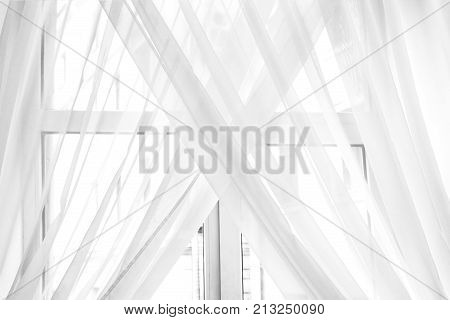 White sheer curtain texture background in daylight atmosphere of apartment's interior. Black and white transparent curtain background.Curtain made of a light fabric that filters the light entering a room.