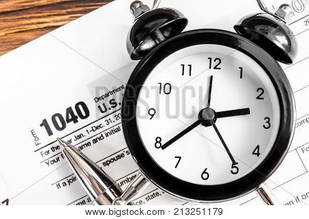 Clock pen and tax forms on the table. Close up. Top view. Tax payment concept.