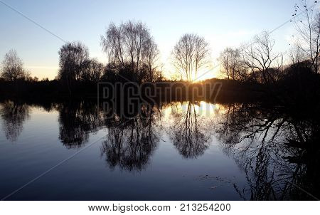 Beautiful natural landscape with silhouettes of trees with branches without leaves near a calm lake in the autumn evening at sunset against the sunlight