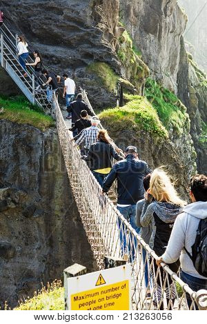 Carrick-a-Rede Rope Bridge, Northern Ireland - JUN 5: Thousands of tourists visiting Carrick-a-Rede Rope Bridge on Jun 5, 2016 in Antrim, Northern Ireland. Hanging 30m above rocks and spanning 20m