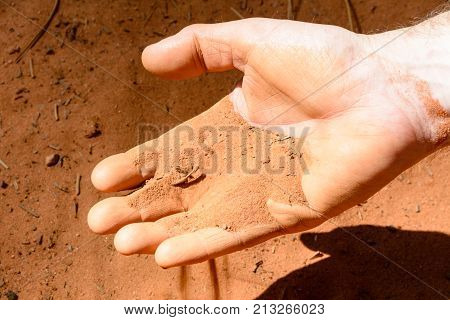 The ocher-colored sand that slips away from the hand of a man in the Roussillons park in Provence