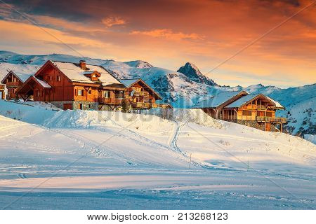 Amazing winter sunset landscape and ski resort with spectacular wooden houses in French Alps Alpe D Huez France Europe