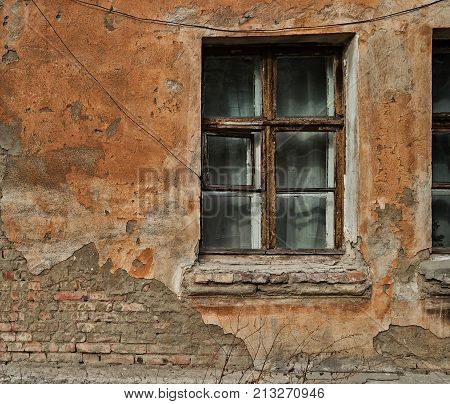 Fragment of old house with a window. Old architecture.Old house. Grunge architecture.Ancient architecture. Old brick house. Grunge old house. Grungy.