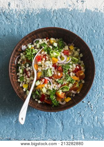 Israeli cous cous ptitim vegetables tabbouleh salad on a blue background top view. Vegetarian food concept
