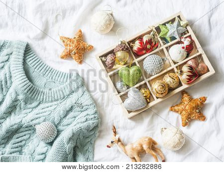 Christmas background. Box of vintage christmas decorations and blue knitted sweater on the bed view from above. Christmas cozy mood still life