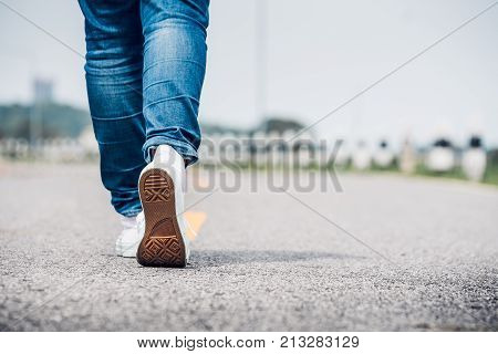 Close up woman wear jean and white sneaker walking forward on highway road in sunny dayAlone travel or solo traveler concept.