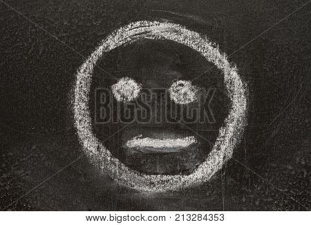 Indifferent icon. Expressionless emoticon face. Neutral smiley mood sketched with white chalk on the blackboard.