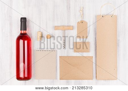 Corporate identity template for wine industry blank beige kraft packaging stationery merchandise set with bottle rose wine on soft white wood background.