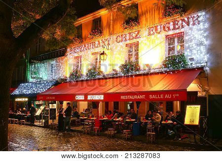 PARIS , France- November 11, 2017: View of typical paris cafe in Paris. Montmartre area is among most popular destinations in Paris, Chez Eugene is a typical cafe.