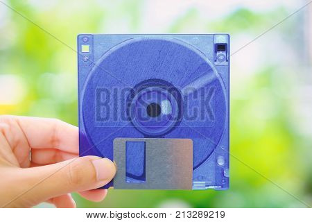 Hand holding a floppy disk against blurred background, old technology and legacy industrial computer equipment