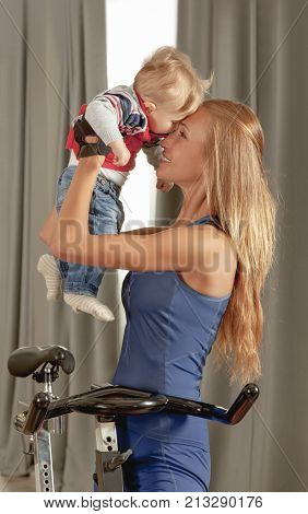 Young beautiful mother having fun embracing her cute  little boy with affection in a cycling gym.