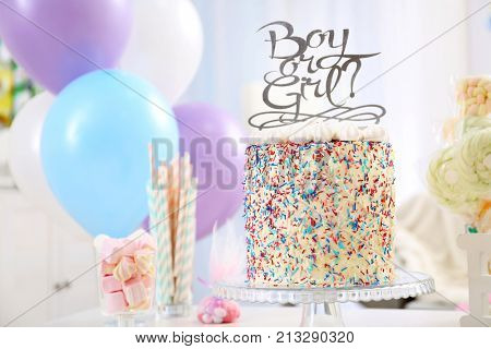 Tasty boy or girl cake for baby shower party on stand