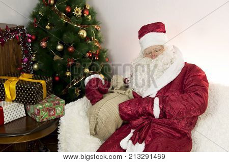 Tired Santa Claus Is Sitting On The Sofa.