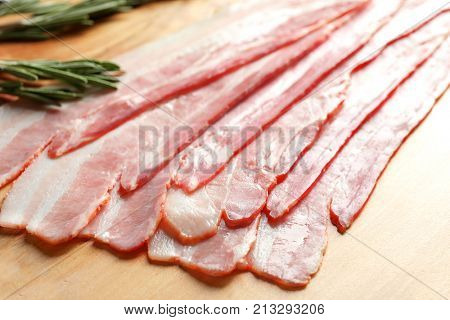 Rashers of bacon on wooden board, close up