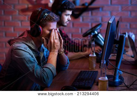 Loss control. Selective focus of upset young gamer in headphones is sitting at table while closed face by hands and expressing disappointment. Serious bearded guy is playing in background. Copy space