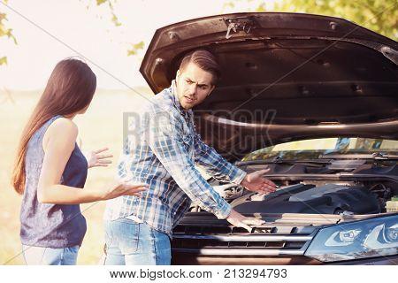 Young couple quarreling near broken car