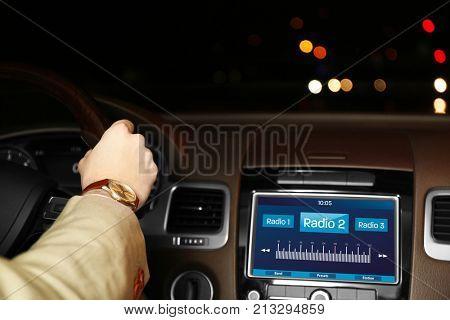 Man listening to radio while driving car at night