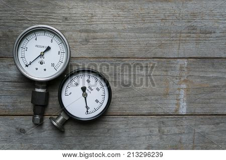 pressure gauge on wood table background, top view