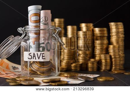Coins in glass jar with bills, copy space. Money box, saving money for dream, pension, vacation. Financial stability concept