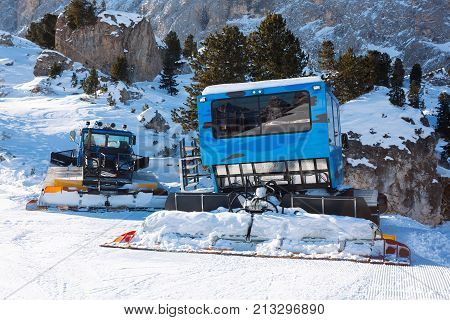 Blue ratrac machine for skiing slope preparations in the mountains. Snow groomers for ski slopes preaparation in winter resort.