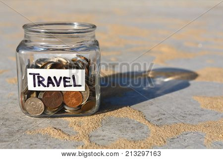 Glass jar with coins for travel on gray floor with sand background, copy space. Money box, distribution of cash savings concept.