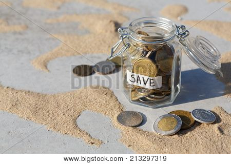 Coins in glass jar on gray floor with sand background, copy space. Money box, saving money for dream, pension, vacation. Financial stability concept